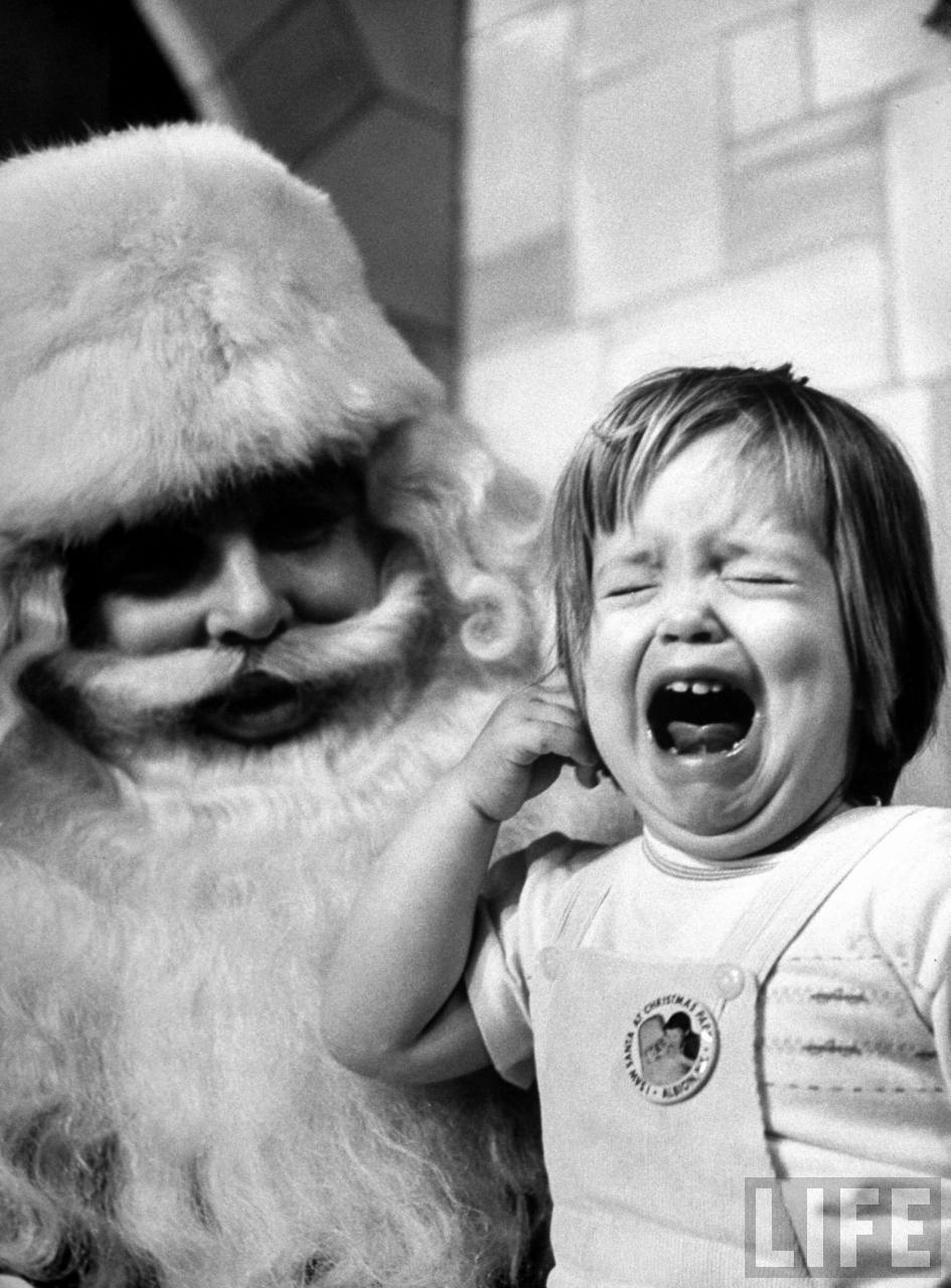 Ken Berends, a Santa Claus in training, looking bewildered at wailing little girl, during practice session for his Santa certificate during 5-day, $75-course at Santa school to enable him to get Yultide jobs at local department stores.