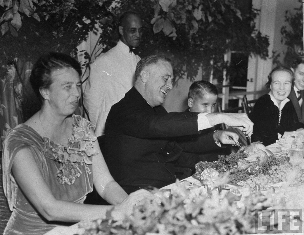 President Franklin D. Roosevelt and his family, smiling and laughing during Thanksgiving dinner. Photographer:Thomas D. Mcavoy. © Time Inc