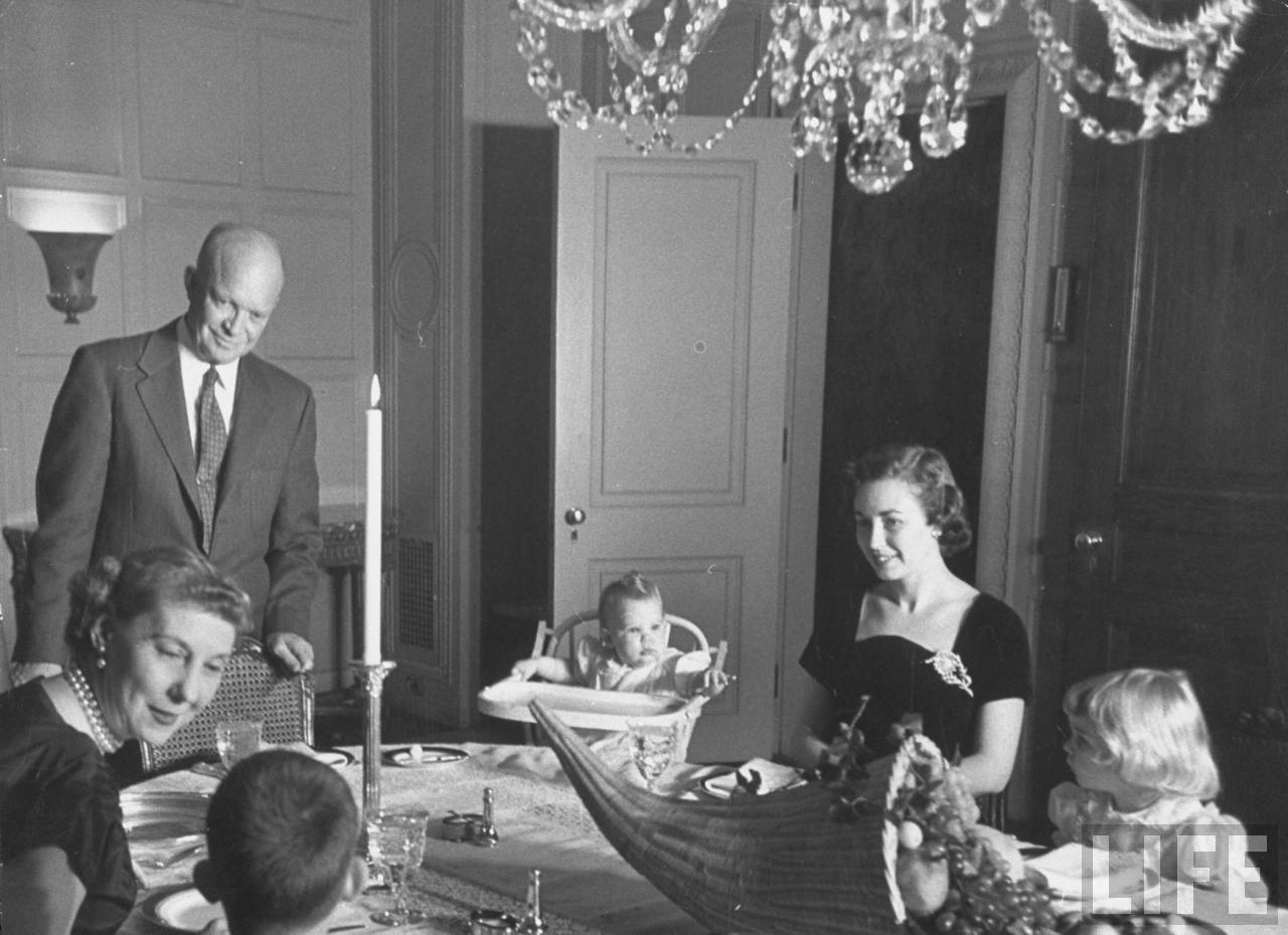 Dwight D. Eisenhower (L, Standing) and family, celebrating Thanksgiving, with cornucopia placed on dinner table.Photographer:Yale Joel. © Time Inc