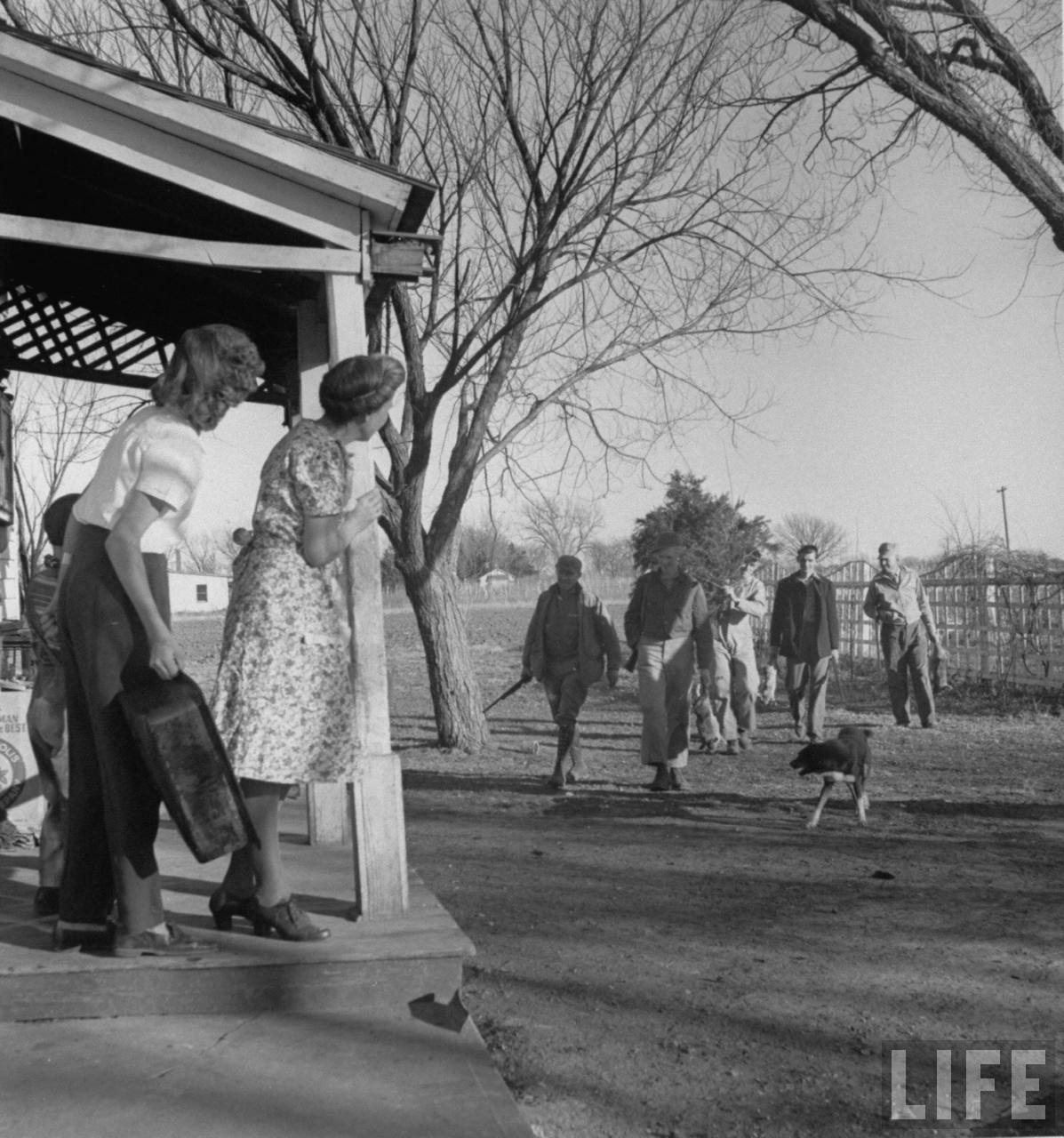 Mrs. James Ferdinand Irwin (2L) standing on porch watching the men in her family, most recently returned fr. service in WWII, carrying home freshly shot rabbits and a cedar tree for Christmas family reunion.© Time Inc. Myron Davis