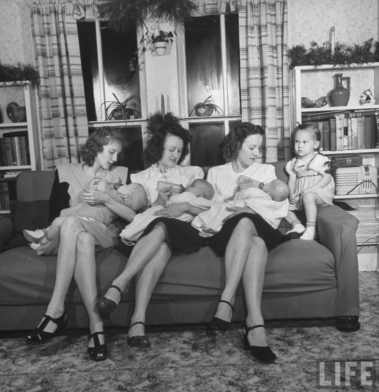 Daughters of James Ferdinand Irwin bottle-feeding their babies at Christmas family reunion celebration marking the return of Irwins sons from service in WWII, L-R: Jeanne Haney & son Joe, Myra Lee Love & son John, Betty Roush and her daughters Julia Ann.© Time Inc. Myron Davis