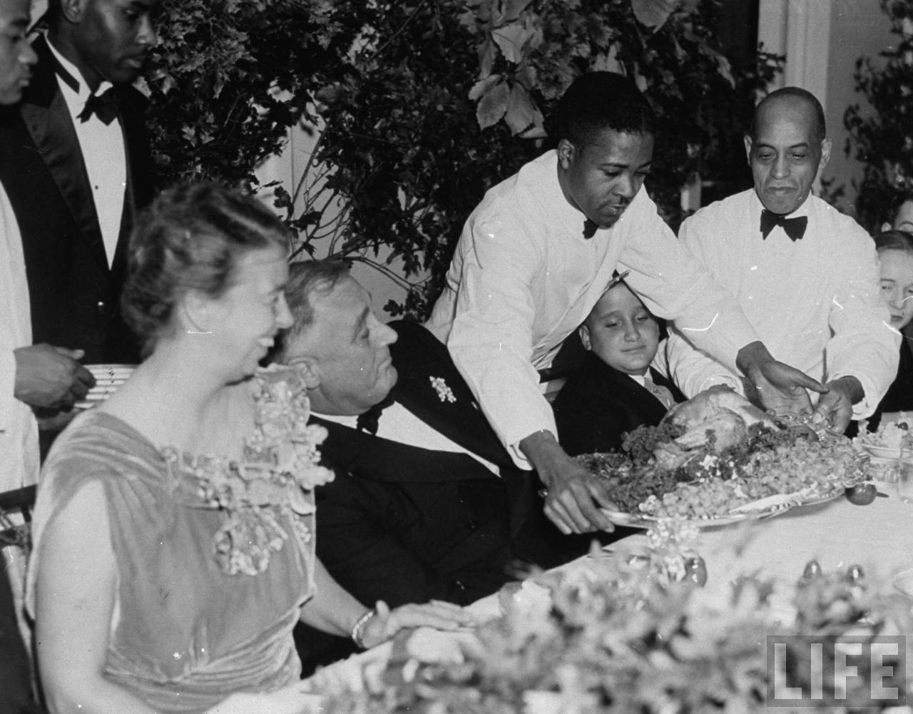 President Franklin D. Roosevelt (C), ducking as the Thanksgiving turkey takes the throne. Photographer:Thomas D. Mcavoy. © Time Inc