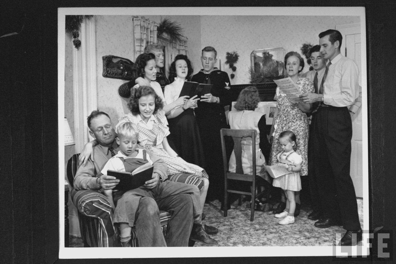 James Ferdinand Irwins family singing carols at early family reunion Christmas celebration marking safe return of sons fr. WWII (L-R) Mr. Irwin, Scotty, Carolyn, Betty Roush, Jim, Myra Lee Love, Jack, Jeanne Haney, Mrs. Irwin, Jeff Haney, Levern Love, I.I. ris Beth Love.© Time Inc. Myron Davis