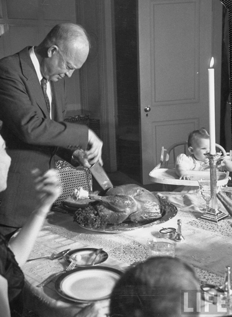 Dwight D. Eisenhower carving the turkey at a family Thanksgiving dinner.Photographer:Yale Joel. © Time Inc