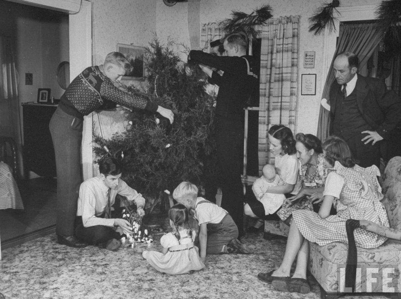 Members of farmer James Ferdinand Irwins family trimming native cedar Christmas tree in living room during family reunion and early Christmas celebration marking the return of Irwins sons and sons-in-law fr. service in WWII.© Time Inc. Myron Davis