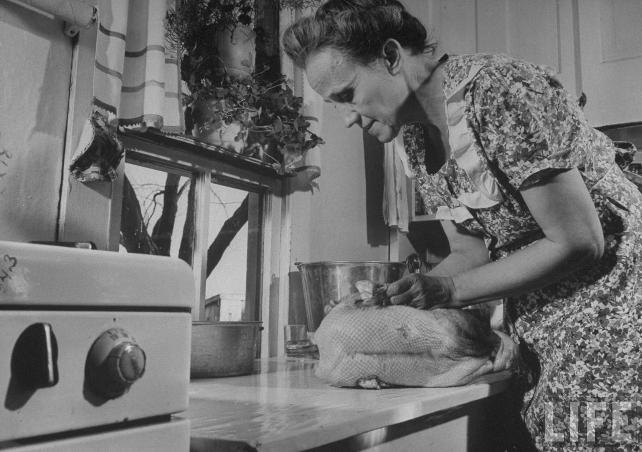 Mrs. James Ferdinand Irwin in kitchen preparing stuffed goose for Christmas dinner that marks the first family reunion in years w. her sons safely returned fr. WWII.© Time Inc. Myron Davis