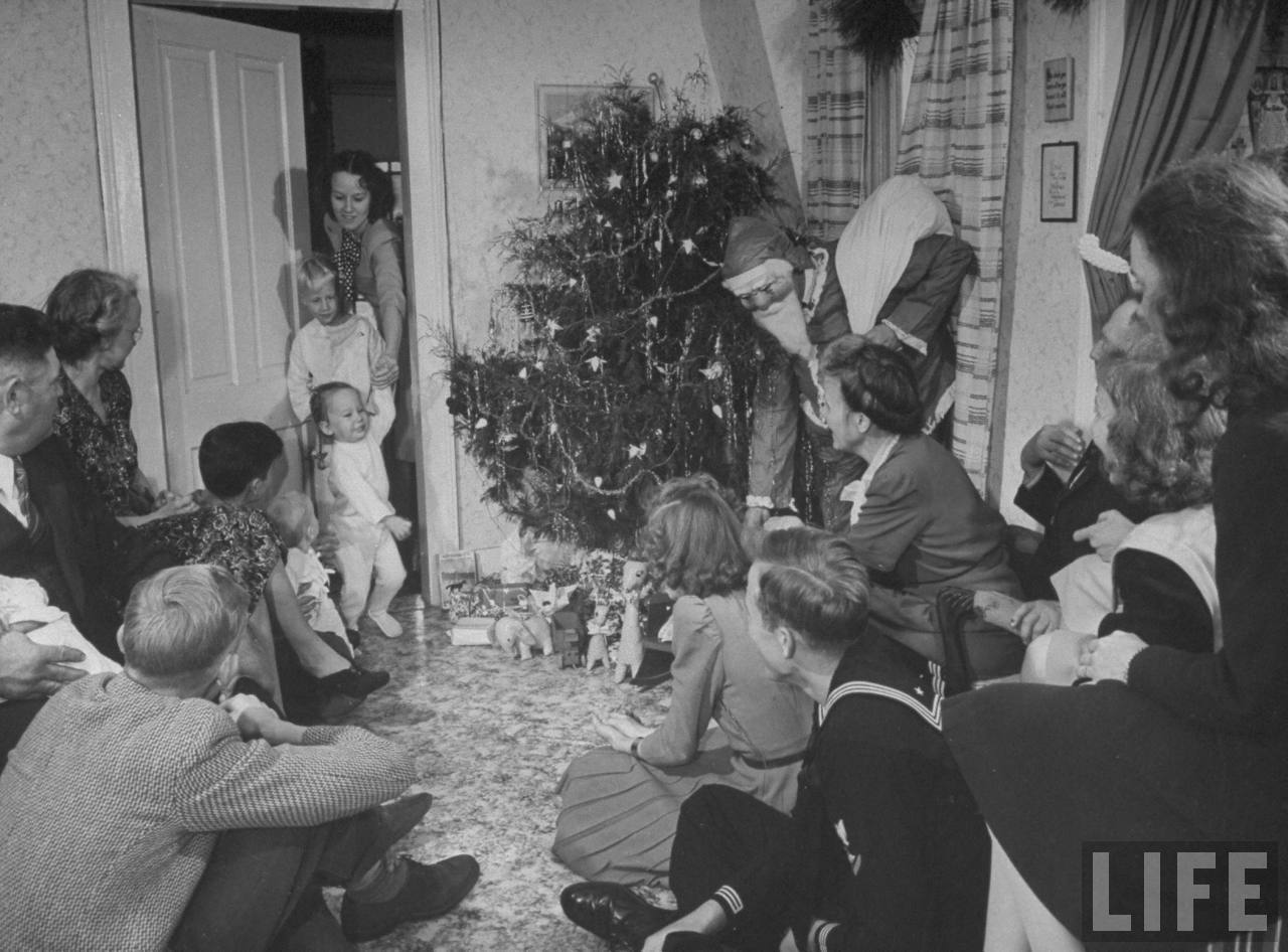 Adult members of farmer James Ferdinand Irwins family gathered nr. tree watching his brother-in-law Fred Andrews (in Santa Claus costume) give presents to young family members at early Christmas family reunion marking safe return of sons fr. service in .WWII.© Time Inc. Myron Davis